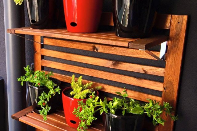 Red and black pots on timber outdoor pot stand in Mount Waverley balcony garden