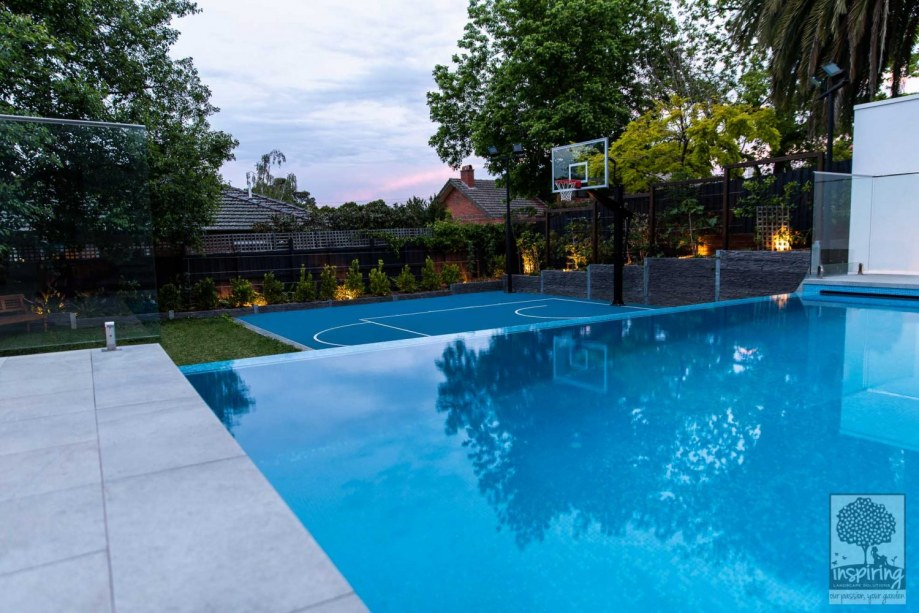 Side view of backyard, basketball court and mini fruit orchard from lap pool in Camberwell garden design