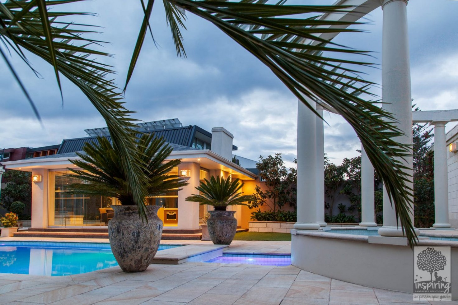 Brighton landscaped pool at night with lights on and styled with pots