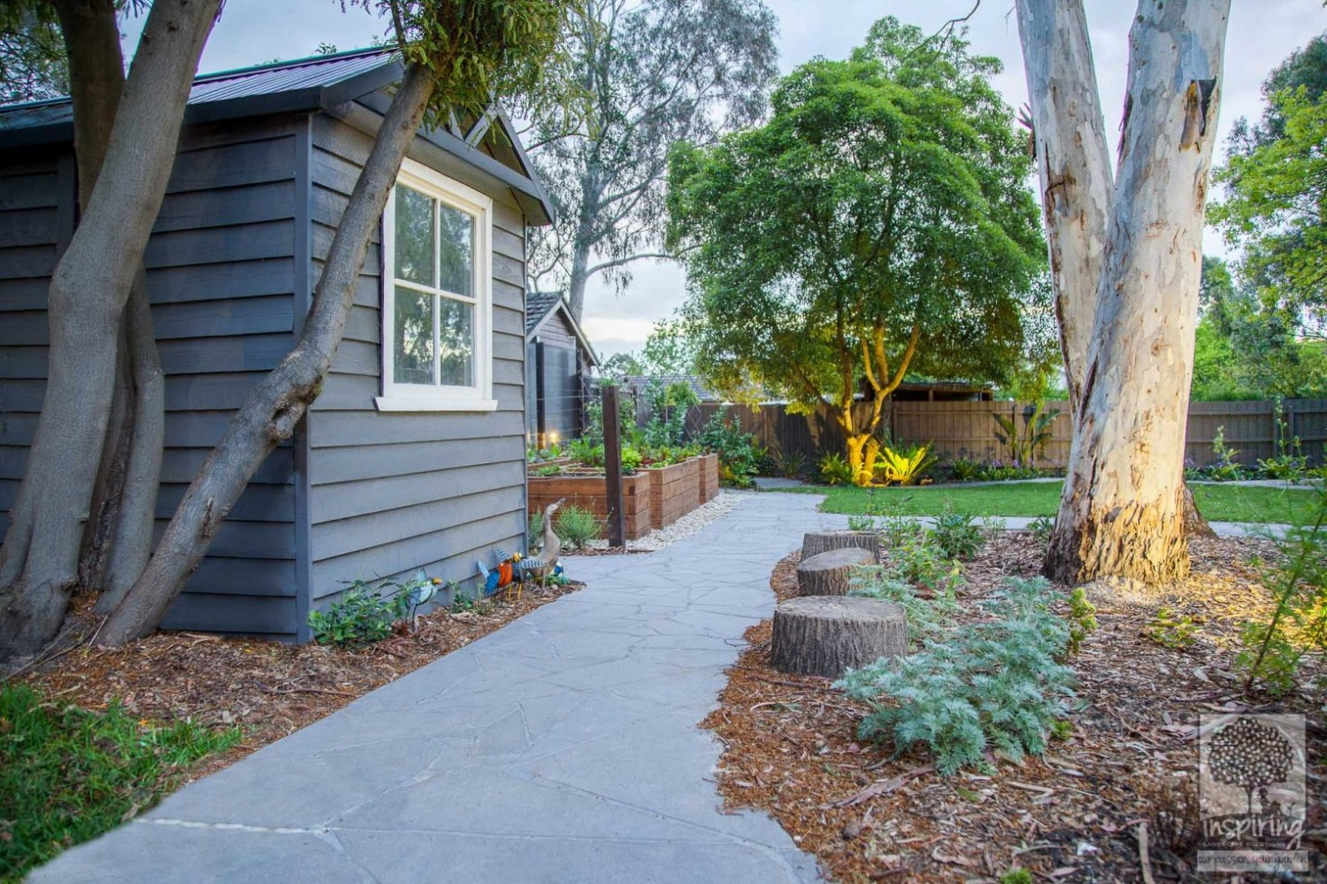 Backyard with crazy paving designed for kids with vegetable patch after landscaping by Inspiring Landscape Solutions Melbourne.