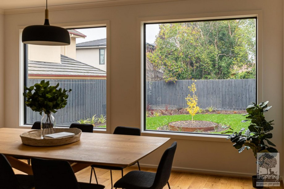 View of gingko tree and grasses in backyard from dining area in Burwood landscape design by Parveen Dhaliwal