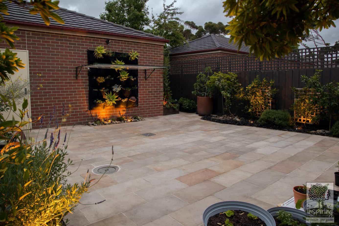 Bundoora courtyard garden design with sandstone paving lit at night