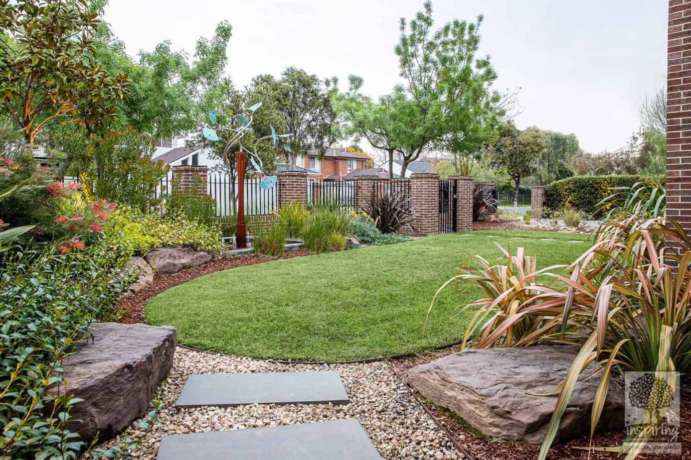 Glen Waverley front garden design with lawn, large rocks and mixed planting of exotics and native Australian plants
