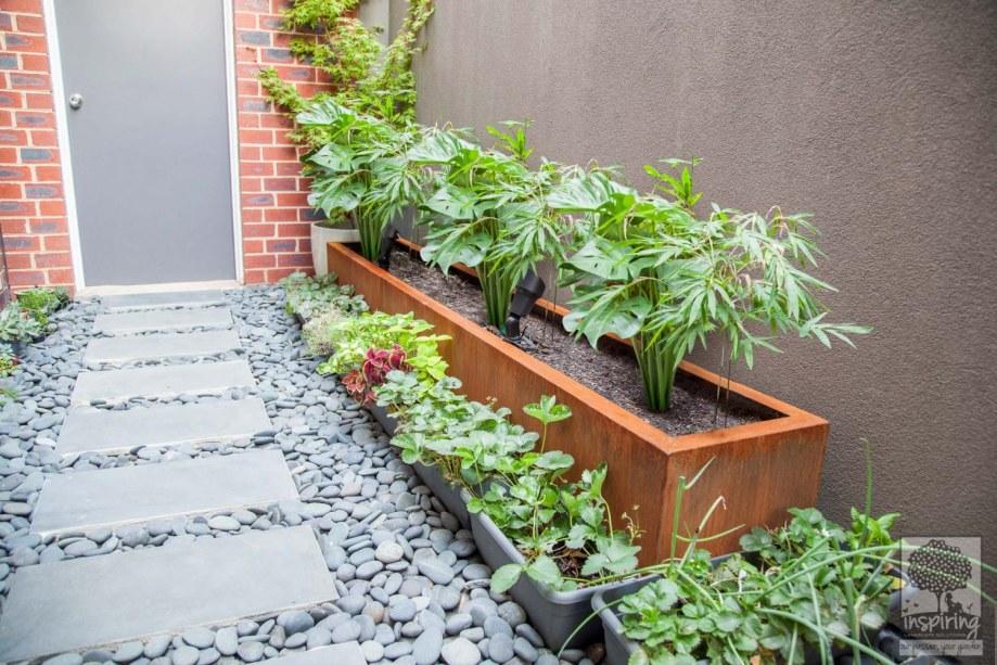Rusty metal fence planter box used in Kew garden design