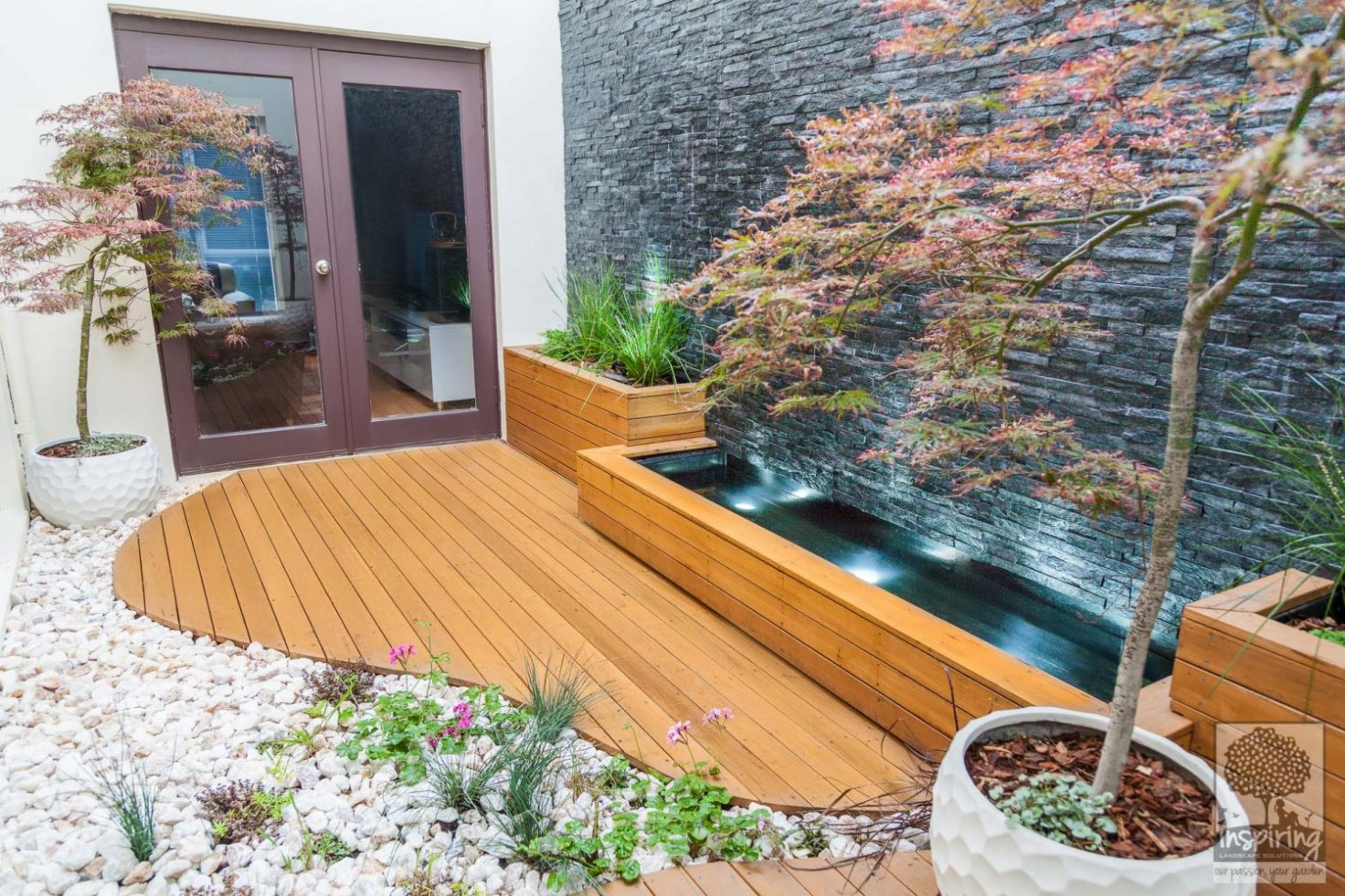 Custom deck shaped like a river bed joining a wall to wall cascading water feature in Maribyrnong landscape design